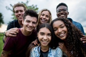 A multi-ethnic group of teenagers are outdoors on a cloudy day. They are wearing casual clothing. They are smiling while taking a selfie together.