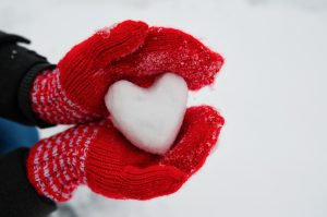 red female gloves hold a white heart from the snow.