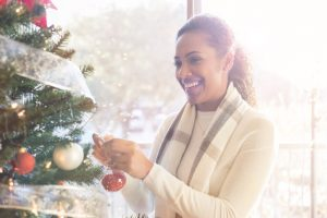Beautiful woman hangs ornament on Christmas tree at home