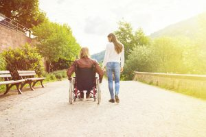 Young couple in wheelchair strolling in a park along the banks of the river