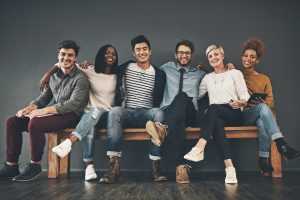 Studio shot of a diverse group of creative young adults embracing each other against a grey background
