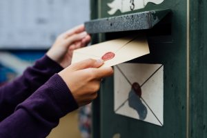 Mailing letter with wax seal to old postbox on street