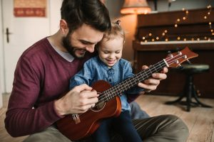 Daughter and father playing guitars