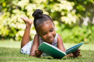 Little girl reading a book lying at park