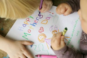 Two young children a coloring a card with crayons for their mom that says Happy Mother's Day.