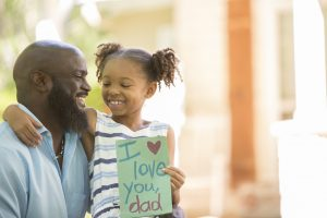 Happy Father's Day. Little girl gives homemade card to her dad in front yard of family home.