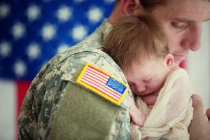 Soldier in uniform holding a newborn baby
