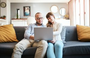 Cropped shot of a young couple using a laptop while relaxing on the sofa in the living room at home
