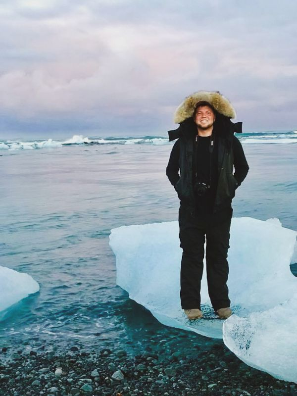 Ryan Standing on a Piece of Glacial Ice on the Beaches of Iceland