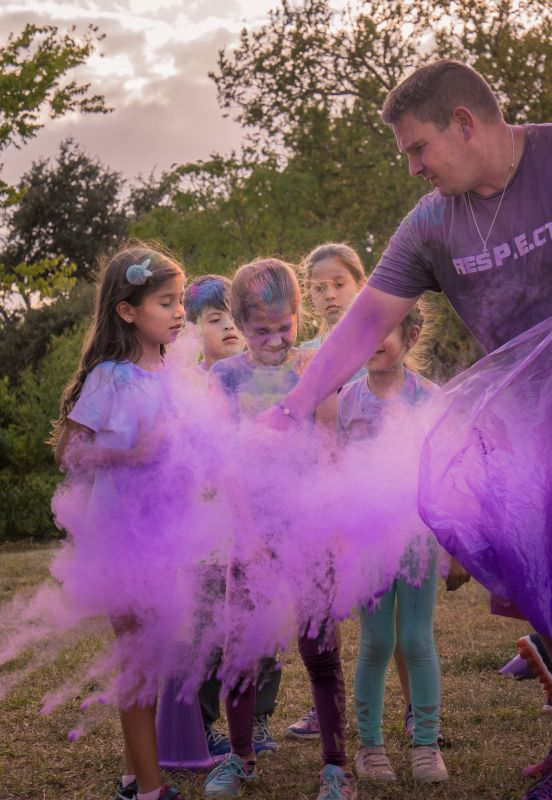 Chace Is in Charge of the Color Run Each Year.  He Sprinkles Colored Powder on the Children and Adults as They Run the Track.